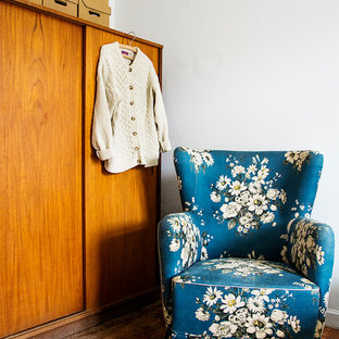 This is an example of a mid-sized midcentury gender-neutral built-in wardrobe with flat-panel cabinets, medium wood cabinets, dark hardwood floors and brown floor.