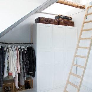 Imagen de vestidor unisex, nórdico, de tamaño medio, con armarios estilo shaker, puertas de armario blancas y suelo de madera pintada