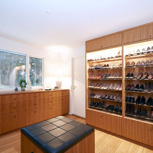 Foto de armario vestidor de mujer, minimalista, con armarios con paneles lisos y puertas de armario de madera oscura