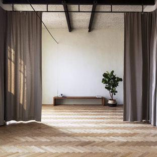 Esempio di un grande studio yoga scandinavo con pareti bianche, parquet chiaro e pavimento beige