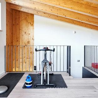 Esempio di una sala pesi moderna di medie dimensioni con pareti bianche, pavimento in legno massello medio e pavimento beige