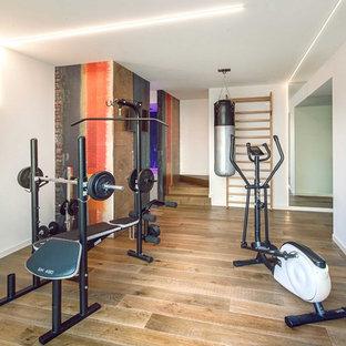 Ispirazione per una sala pesi minimalista con pareti bianche e parquet chiaro