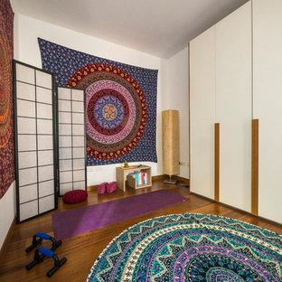 Ispirazione per uno studio yoga eclettico di medie dimensioni con pareti bianche e pavimento in legno massello medio