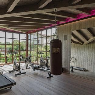 Immagine di una grande palestra multiuso minimal con pareti grigie, pavimento in legno massello medio e pavimento grigio