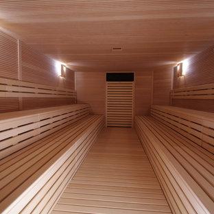 Immagine di una grande palestra multiuso moderna con pareti marroni, pavimento in legno verniciato e pavimento marrone