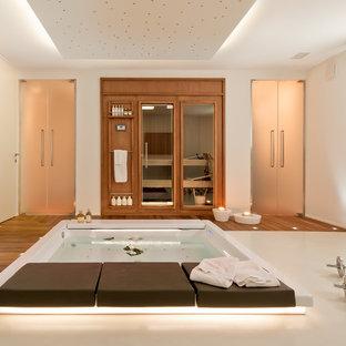 Multifunktionaler Moderner Fitnessraum mit weißer Wandfarbe und braunem Holzboden in Baltimore