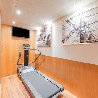 Idee per una piccola sala pesi moderna con pareti multicolore, pavimento in legno massello medio e pavimento marrone