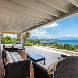 Esempio di un patio o portico tropicale con pedane e un tetto a sbalzo