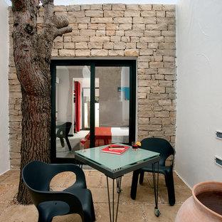 Idee per un piccolo patio o portico mediterraneo in cortile con pavimentazioni in pietra naturale