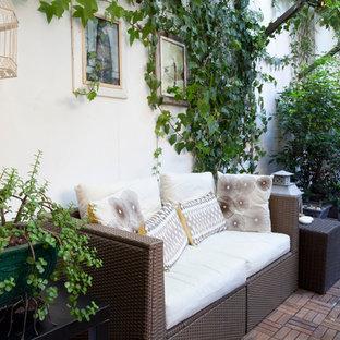 Ejemplo de patio romántico con adoquines de ladrillo