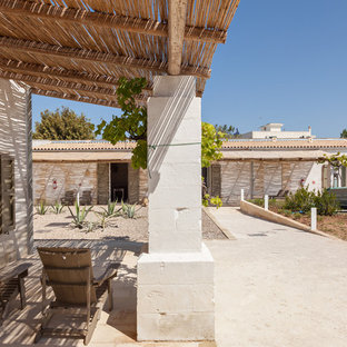 Esempio di un patio o portico mediterraneo in cortile con pavimentazioni in mattoni e una pergola
