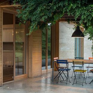 Esempio di un patio o portico minimal di medie dimensioni con lastre di cemento e una pergola