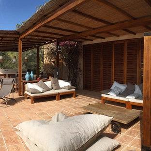 Ispirazione per un grande patio o portico mediterraneo dietro casa con piastrelle e una pergola