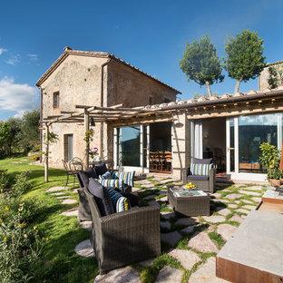 Immagine di un patio o portico country di medie dimensioni con pavimentazioni in pietra naturale e un caminetto