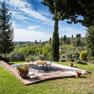 Foto di un ampio patio o portico country con pavimentazioni in mattoni