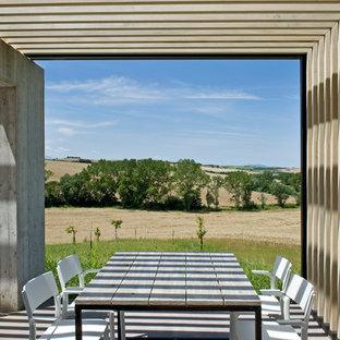 Immagine di un patio o portico moderno di medie dimensioni con lastre di cemento e una pergola