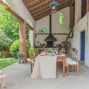 Ispirazione per un patio o portico classico con lastre di cemento e un tetto a sbalzo