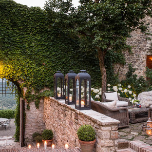 Esempio di un grande patio o portico in campagna con pavimentazioni in mattoni