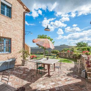 Idee per un patio o portico country nel cortile laterale con pavimentazioni in mattoni, un giardino in vaso e nessuna copertura