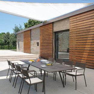 Foto di un patio o portico contemporaneo dietro casa con lastre di cemento e nessuna copertura