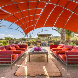 Ispirazione per un patio o portico mediterraneo dietro casa con lastre di cemento e un gazebo o capanno