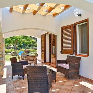 Idee per un patio o portico mediterraneo con piastrelle