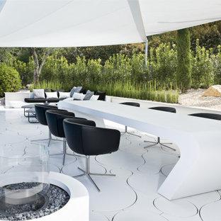 Foto di un grande patio o portico minimalista dietro casa con un focolare e un gazebo o capanno