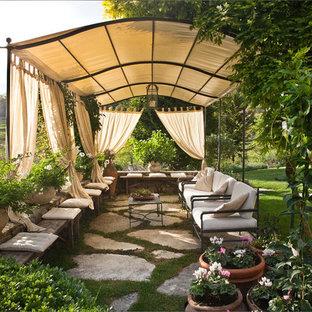 Ispirazione per un grande patio o portico country con pavimentazioni in pietra naturale, un giardino in vaso e un parasole