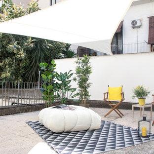 Immagine di un patio o portico contemporaneo con pavimentazioni in cemento e un parasole