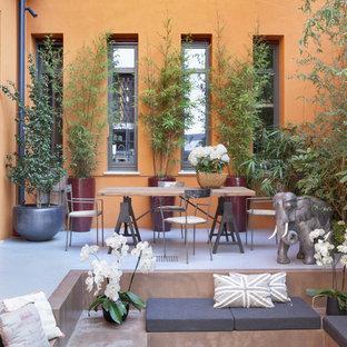 Idee per un patio o portico eclettico dietro casa con lastre di cemento e nessuna copertura