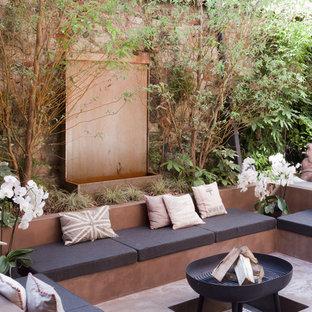 Immagine di un patio o portico bohémian dietro casa con un focolare, lastre di cemento e nessuna copertura