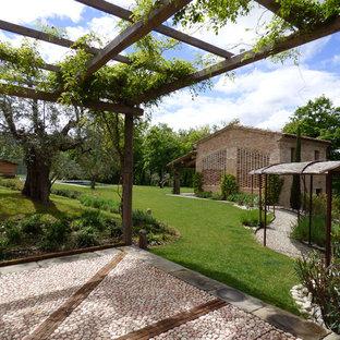 Immagine di un ampio patio o portico country con una pergola