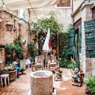 Inspiration for a country courtyard patio in Venice with brick paving and an awning.