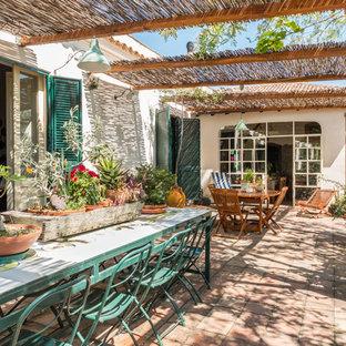Foto di un patio o portico mediterraneo con un giardino in vaso, pavimentazioni in mattoni e una pergola