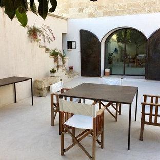 Foto di un patio o portico mediterraneo in cortile con nessuna copertura e lastre di cemento