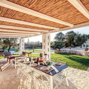 Foto di un patio o portico mediterraneo dietro casa con un tetto a sbalzo e con illuminazione