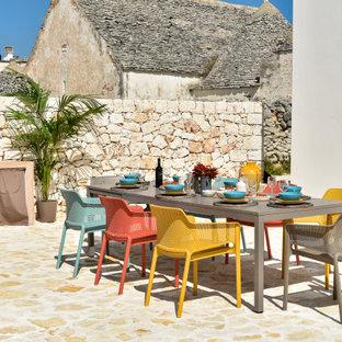 Idee per un grande patio o portico mediterraneo con pavimentazioni in pietra naturale e nessuna copertura