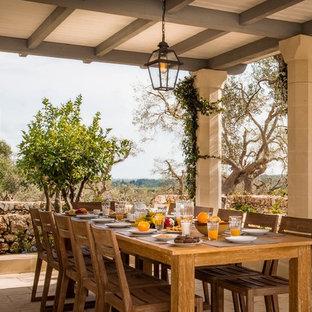 Foto di un patio o portico mediterraneo con piastrelle, un tetto a sbalzo e con illuminazione