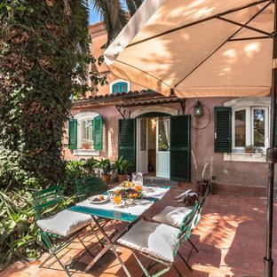 Foto di un patio o portico mediterraneo di medie dimensioni e dietro casa con piastrelle