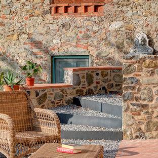 Esempio di un patio o portico mediterraneo con un giardino in vaso, ghiaia e nessuna copertura