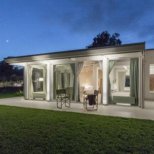 Immagine di un patio o portico design con lastre di cemento