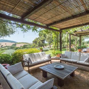 Foto di un grande patio o portico country nel cortile laterale con pavimentazioni in mattoni e una pergola