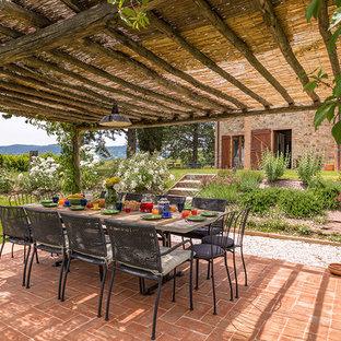 Esempio di una veranda country con pavimento in mattoni