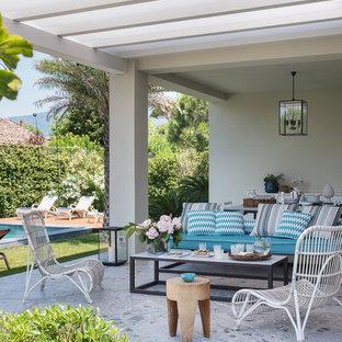 Esempio di un patio o portico stile marinaro di medie dimensioni e dietro casa con pavimentazioni in pietra naturale e una pergola