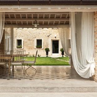 Foto di un patio o portico country dietro casa con pavimentazioni in cemento