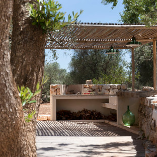 Design ideas for a small mediterranean patio in Milan with an outdoor kitchen, a pergola and natural stone paving.