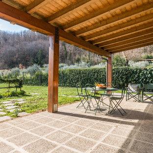 Ispirazione per un patio o portico mediterraneo dietro casa con pavimentazioni in cemento e un parasole