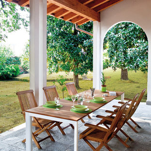 Esempio di un patio o portico country di medie dimensioni con pavimentazioni in pietra naturale e un tetto a sbalzo
