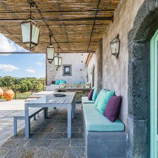 Foto di un patio o portico mediterraneo dietro casa con lastre di cemento e un parasole