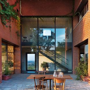 Foto di un ampio patio o portico country dietro casa con pavimentazioni in pietra naturale